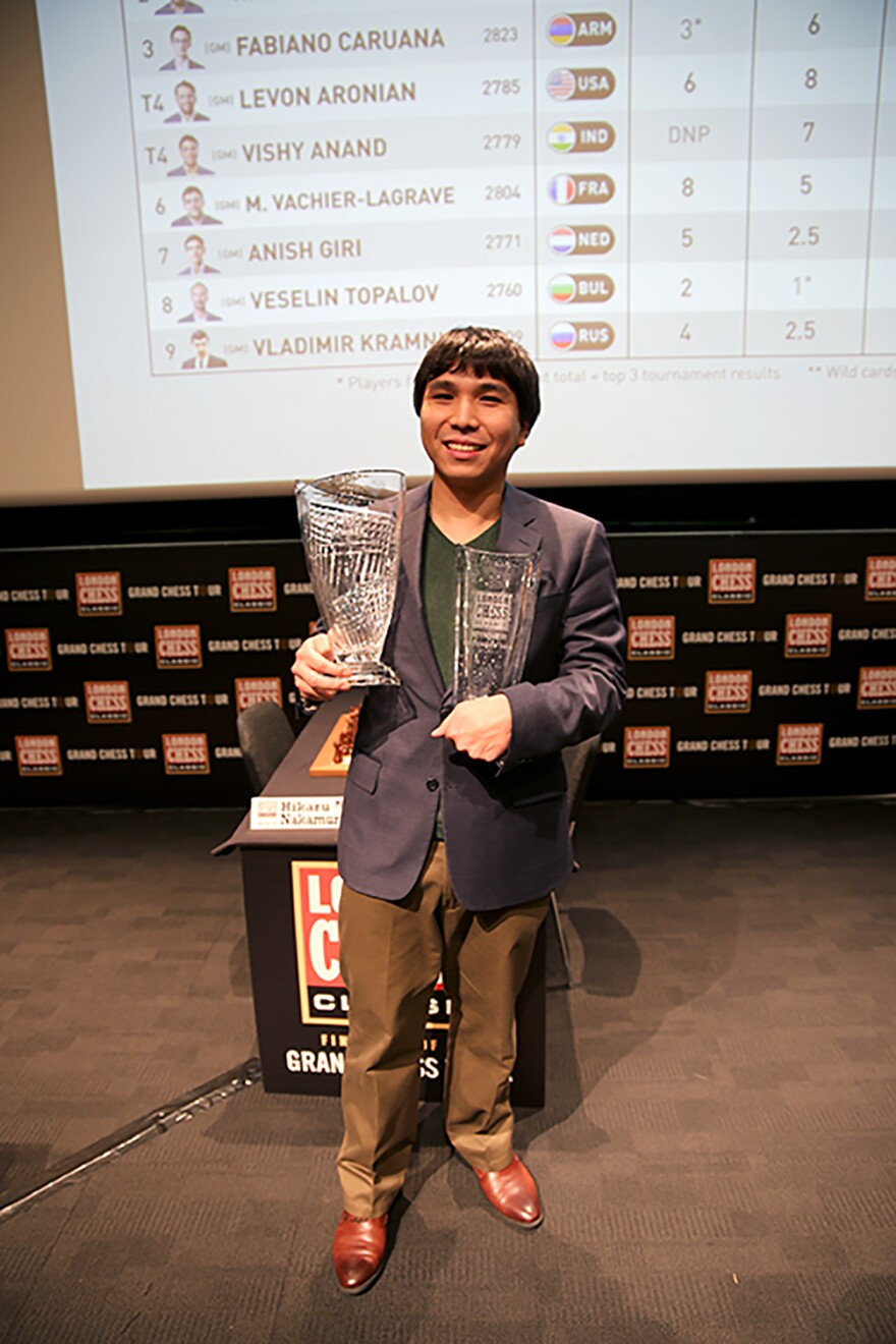 Wesley So holding chess trophies