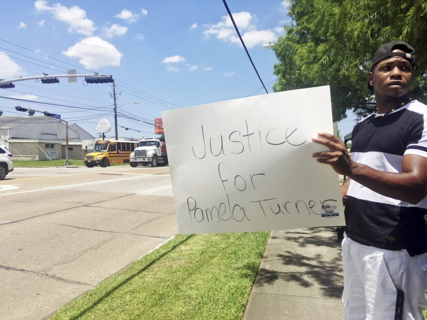 "Man holds a sign that reads ""Justice for Pamela Turner"""