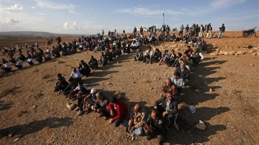 Kurds sit in formation to form the initials of the People's Protection Unit, or YPG, the main Kurdish militia in Syria, on a hilltop overlooking Kobani just over the border, in support of Syrian Kurds fighting ISIS, on Wednesday. Turkey believes the People's Protection Unit have ties to a Kurdish group in Turkey that is the Turkish government considers a terrorist organization.