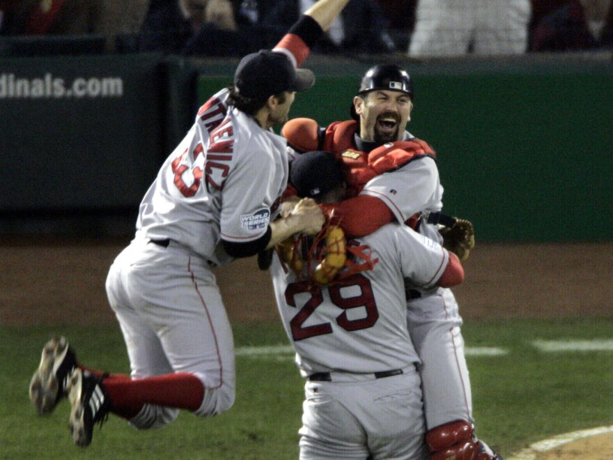 The Boston Red Sox's Doug Mientkiewicz (left) and catcher Jason Varitek (right) jump into Keith Foulke's arms after the Red Sox defeated the St. Louis Cardinals 3-0 in Game 4 to win the 2004 World Series.