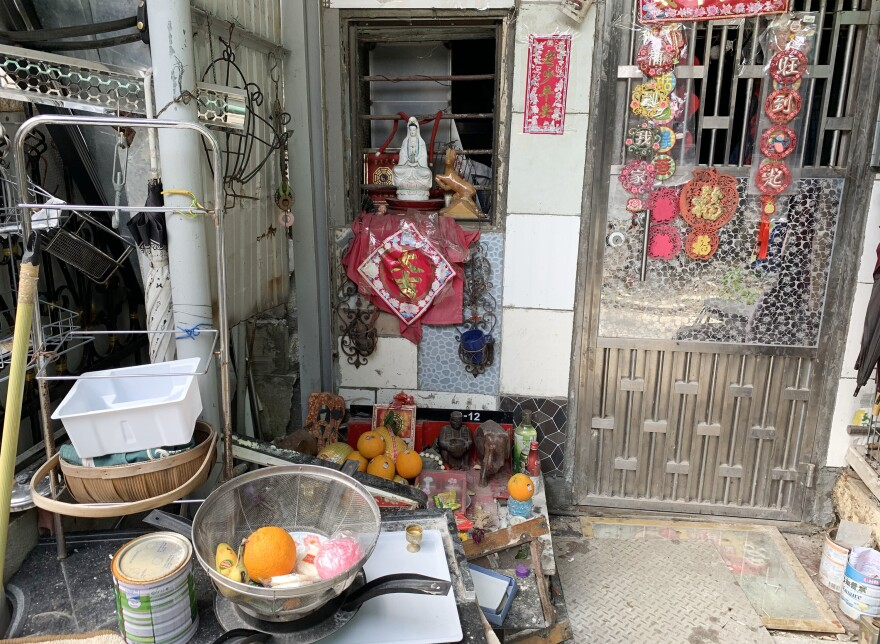A street-level Buddhist shrine sits outside a home in Nam Pin Wai.