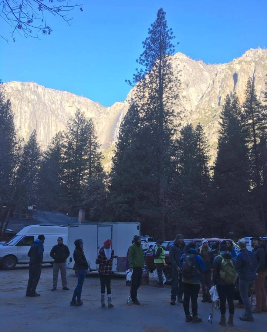 Volunteers pick up litter sticks and supplies in the shadow of Yosemite's Sierra Nevada Mountians.