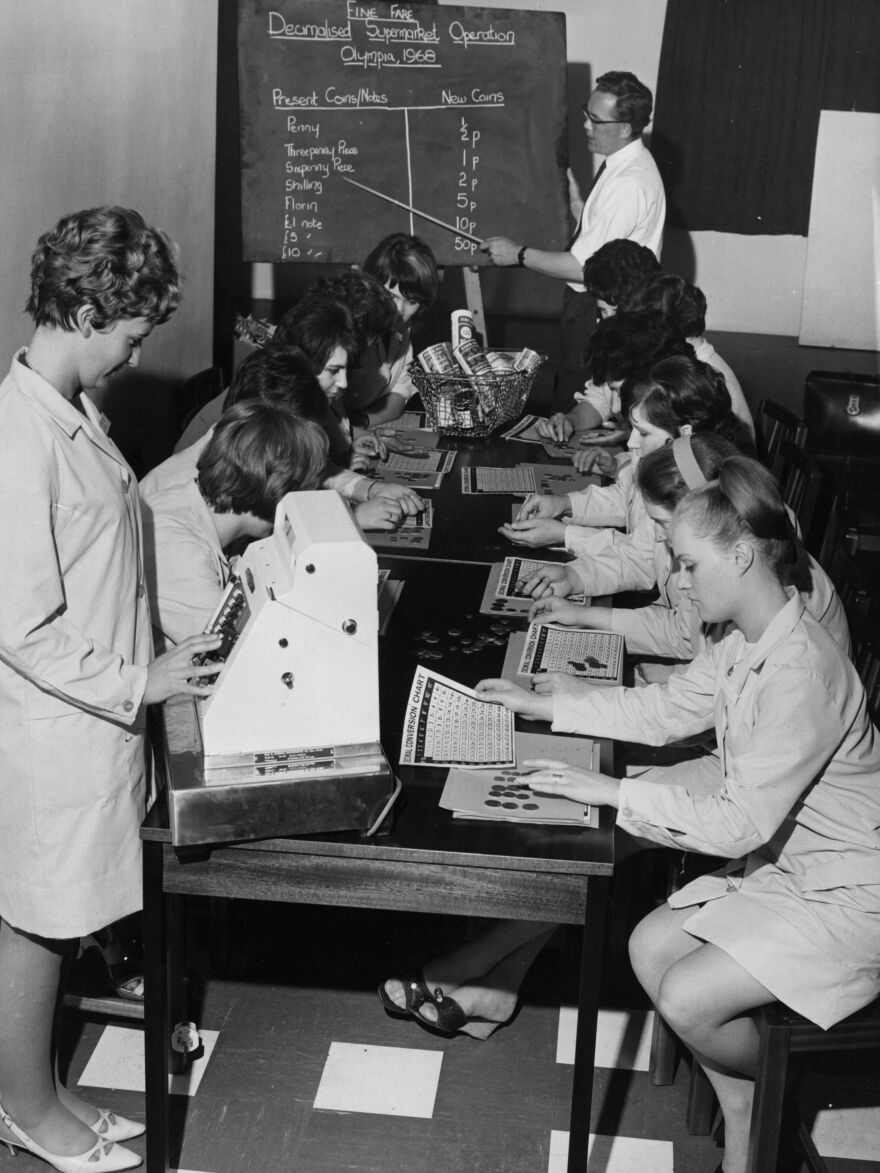 Checkout workers at a Fine Fare supermarket studying decimal conversion charts during a training course in 1968.