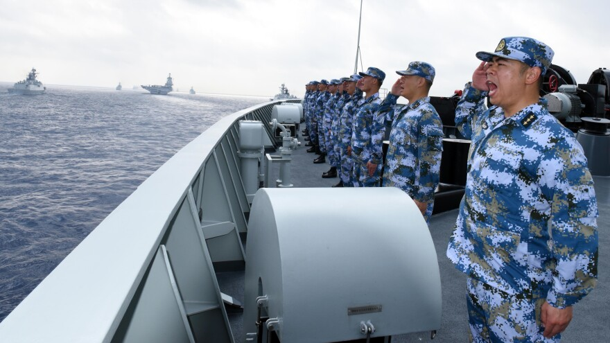 China plans to hold live-fire exercises next Wednesday in the Taiwan Strait. On Thursday, a Chinese navy fleet including the aircraft carrier Liaoning (in background) held a parade in the South China Sea.