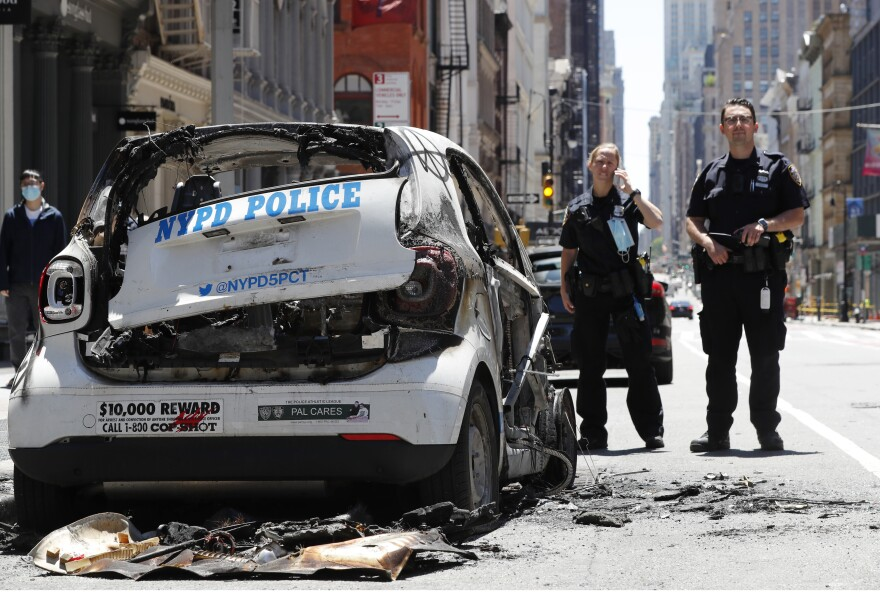 Officers stand guard beside a burned-out mini-New York Police Department vehicle, abandoned on Broadway in Lower Manhattan, Sunday, May 31, 2020, in New York.