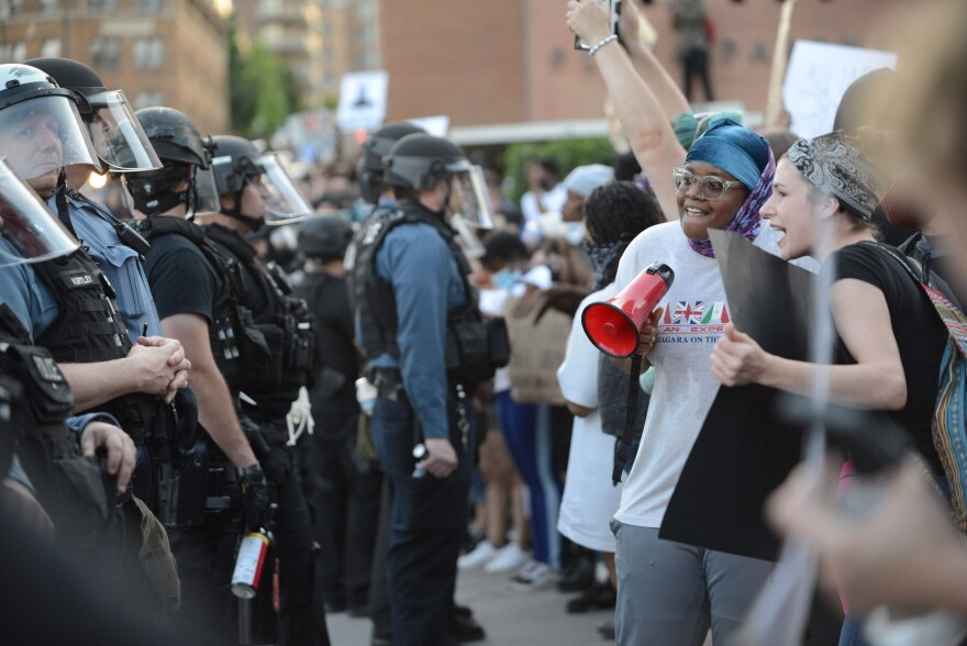 Black and white protesters with bullhorn and signs face a line of Kansas City, Missouri police officers wearing helmets, face shields and vests with some holding cans of pepper spray.