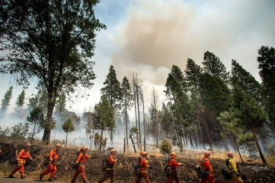 Inmate firefighters battle a California wildfire in July. Qualified inmates can volunteer to be trained in firefighting; in exchange, they are paid $2 a day and an extra $1 per hour when fighting fires. The inmate firefighters also receive sentence reductions.