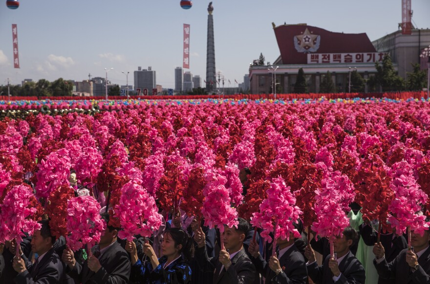 "North Korean civilians wave pink and red artificial flowers and chant ""Kim Jong Un"" on Kim Il Sung Square in Pyongyang during a mass military parade to mark its 70th anniversary as a nation."