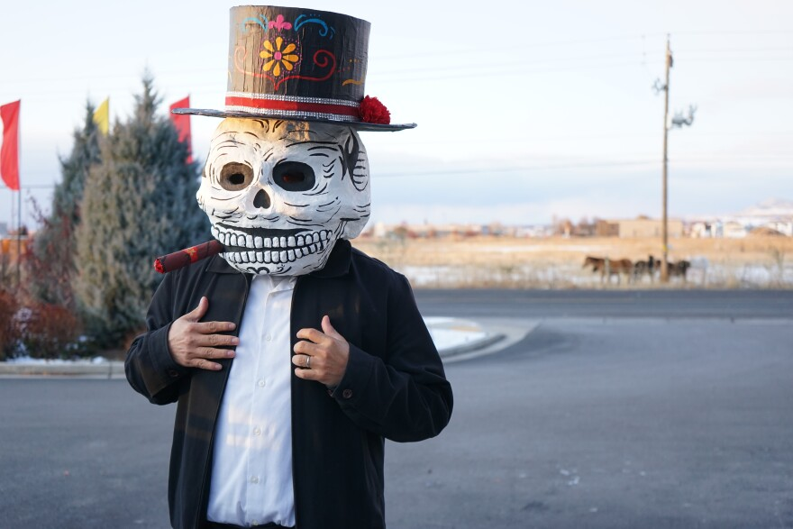 A man wearing a large skeleton make and top hat.