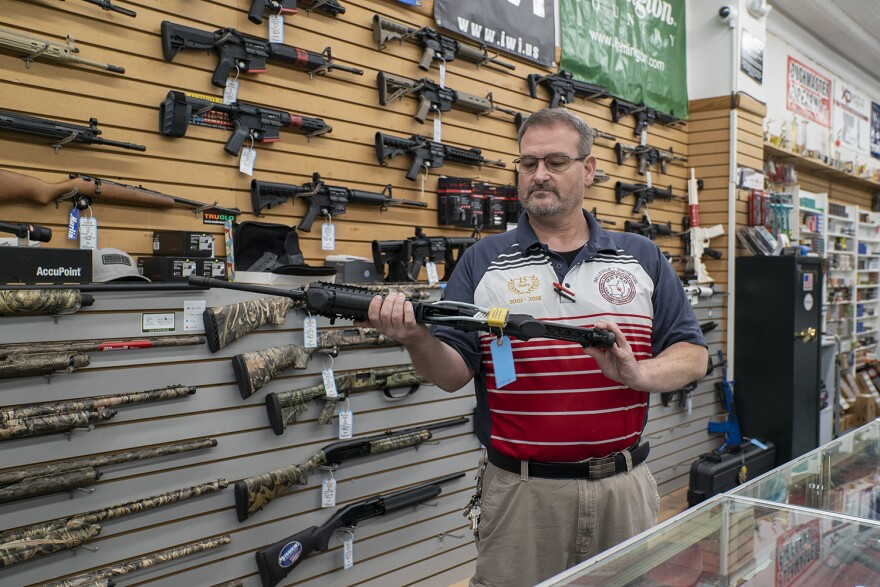 Steven King, owner of Metro Shooting Supplies, inspects one of the firearms in his store. Illinois State Police put new regulations for gun stores in effect this month.