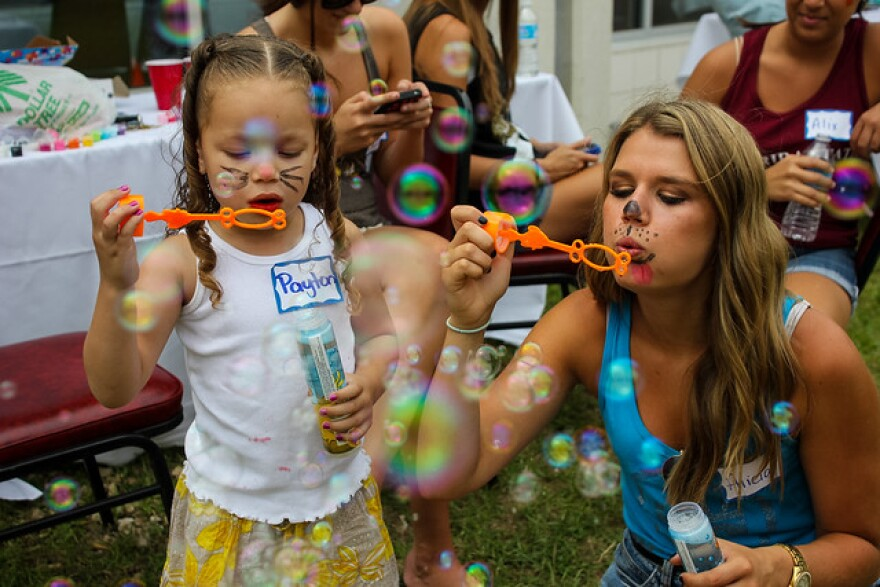 Participants blow bubbles at a Guardian ad Litem Appreciation Day event in Tallahassee.