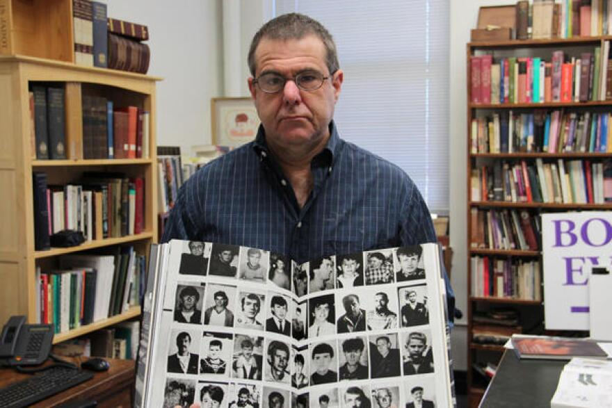 Benjamin Moore of Fontbonne University holds a book with photos of Muslims who lost their lives during the Bosnian War. Moore runs the Bosnia Memory Project.