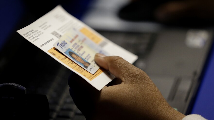 An election official checks a voter's photo identification at an early voting polling site in Austin, Texas.