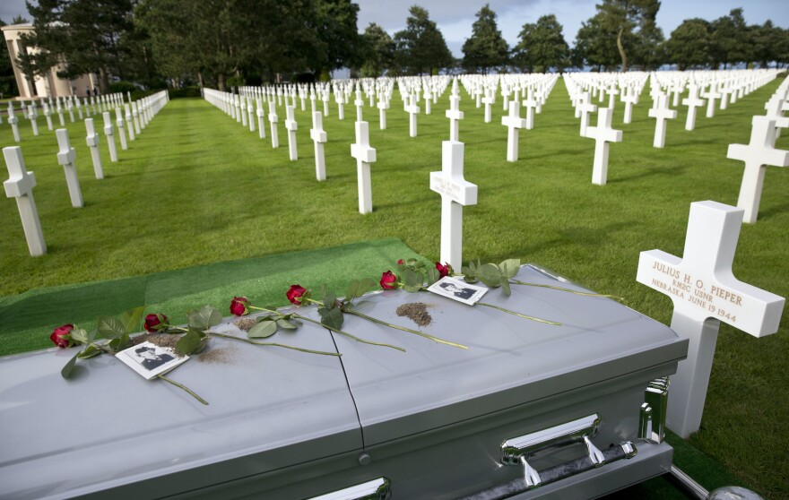 The casket of U.S. Navy sailor Julius Pieper lays next to the grave of his twin brother Ludwig during a reburial service at the Normandy American Cemetery, in Colleville-sur-Mer, France.