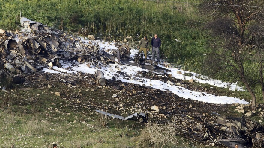 Israeli security stands around the wreckage of an F-16 that crashed in northern Israel on Saturday. The Israeli military shot down an Iranian drone it said infiltrated the country before launching attacks on at least a dozen Iranian and Syrian targets inside Syria.