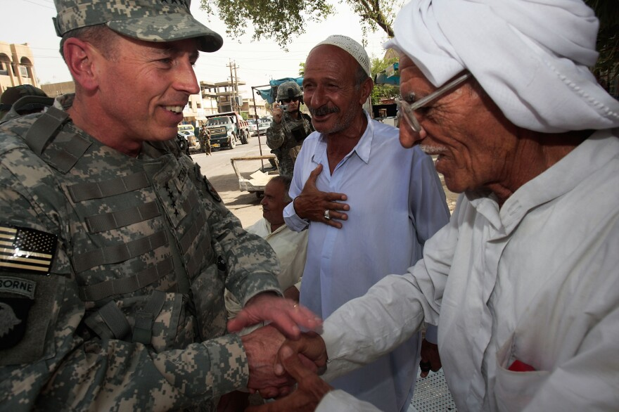 Gen. David Petraeus greets an Iraqi man at a tea shop in Baghdad in 2007. In 2011, Petraeus left the Army to become CIA director. He resigned Friday, citing an extramarital affair.