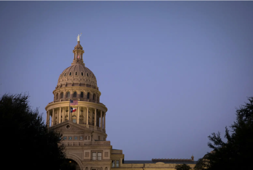 Dome of the Texas Statehouse against a darkening sky. The dome is lit.