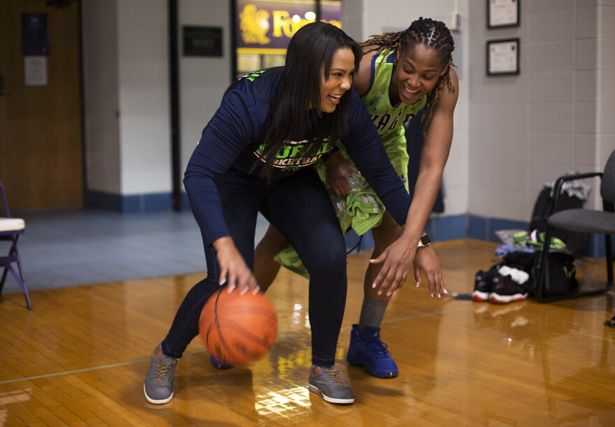 Khalia Collier jokes around with player Jaleesa Butler before the start of the St. Louis Surge's media day.