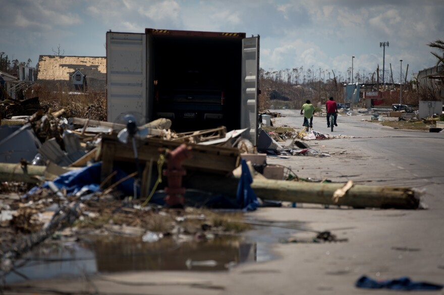 Enock Nelson (left), 30, and Olby Alcy, 25, bike past mangled structures and debris left by Hurricane Dorian, which hit the Bahamas as a Category 5 storm.