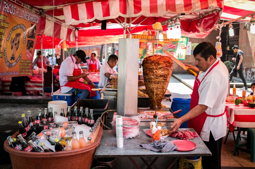 Rich, fatty street food is available all over Mexico. This vendor prepares tacos al pastor, with the meat cooked on a spit, outside a metro station in Mexico City.