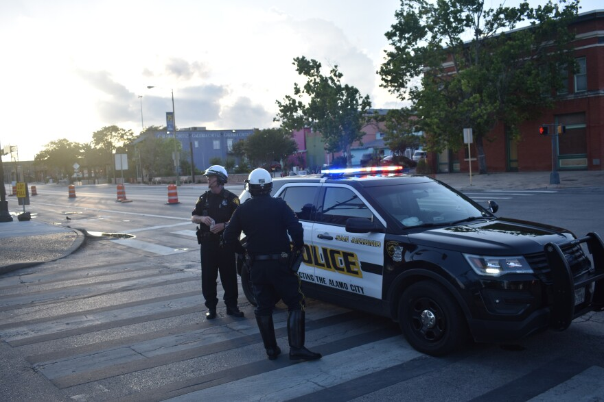 Two San Antonio Police Officers stand in the street near the path of a protest on June 3, 2020.
