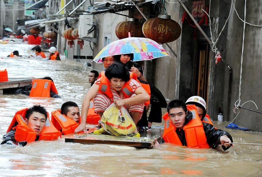 Rescue workers lead people through floodwaters brought by the typhoon in Ningde in Fujian province on Wednesday.
