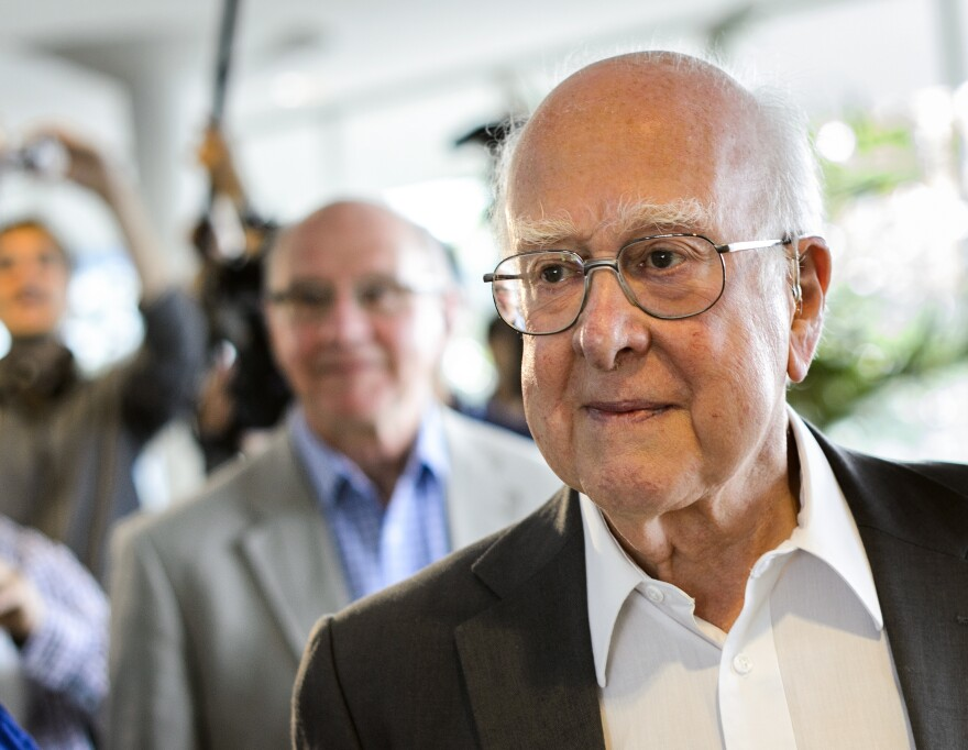 British physicist Peter Higgs, right, arrives for the opening of a seminar to deliver the latest update in the 50-year bid to explain a riddle of fundamental matter in the search for a particle called the Higgs boson.
