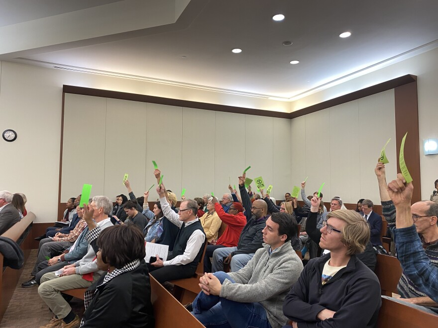 People attending the North Carolina Utilities Commission public hearing for Duke's rate increase wave green cards to agree with a speaker instead of applauding.