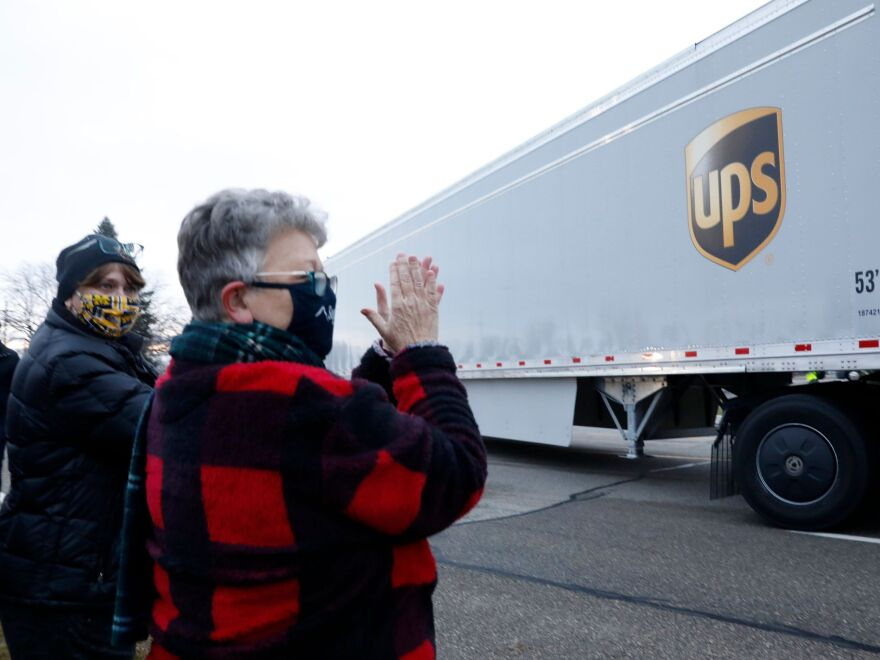 Nancy Galloway and Susan Deur cheer as trucks carrying the first shipment of the COVID-19 vaccine leave Pfizer's Global Supply facility in Kalamazoo, Mich., on Dec. 13, 2020.