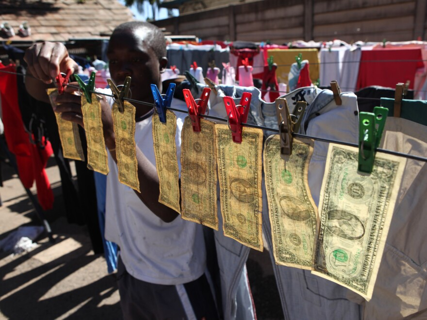 Alex Mupondi, hangs one dollar notes on a drying line after washing them in Harare, Zimbabwe, in 2010, shortly after Zimbabweans began trading in the American currency after the Zimbabwean dollar went into a hyperinflationary spiral.