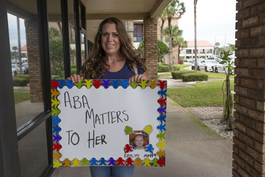A woman holds a sign that says ABA Matters To Her, next to a photo of her young daughter.