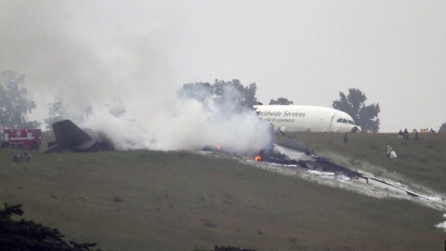 Debris burns as a UPS cargo plane lies on a hill near Birmingham-Shuttlesworth International Airport after crashing Wednesday.
