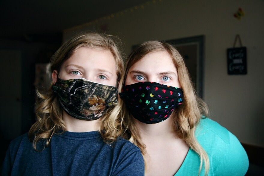 Two females huddle together wearing masks over their noses and mouths