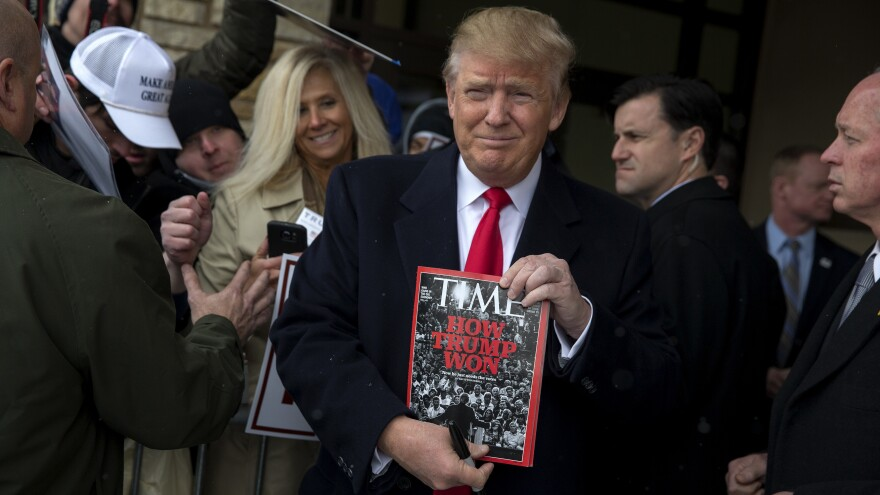 Donald Trump holds a copy of <em>Time</em> magazine in January 2016 in Winterset, Iowa. His golf clubs have displayed fake <em>Time</em> covers featuring Trump.