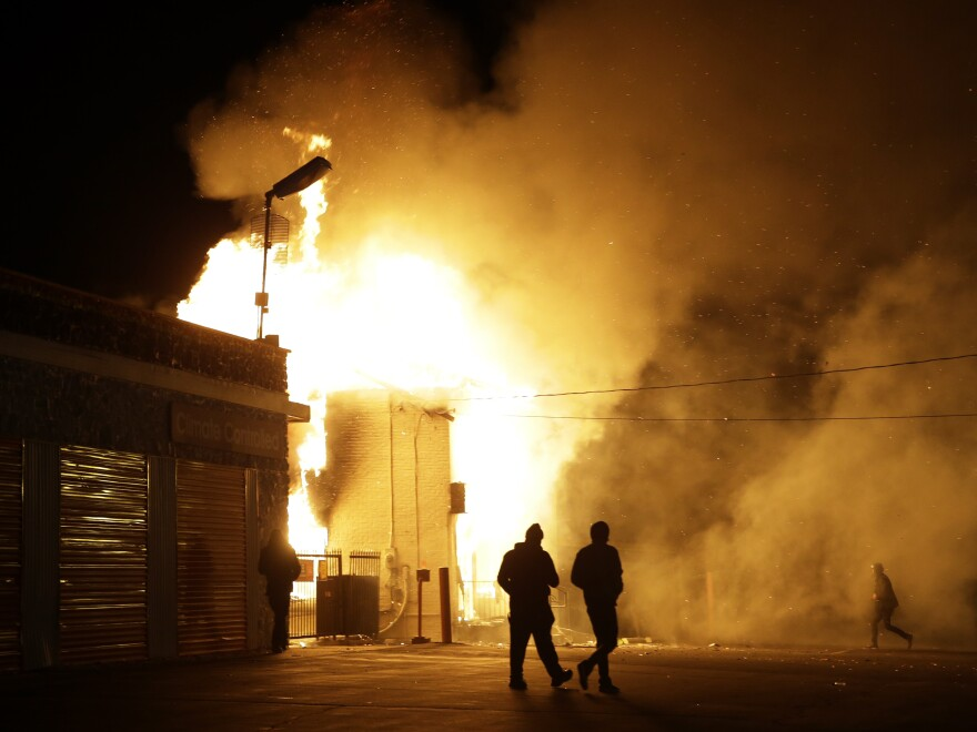 People walk away from a storage facility on fire after it was announced that a grand jury decided not to indict Ferguson police Officer Darren Wilson in the death of Michael Brown.
