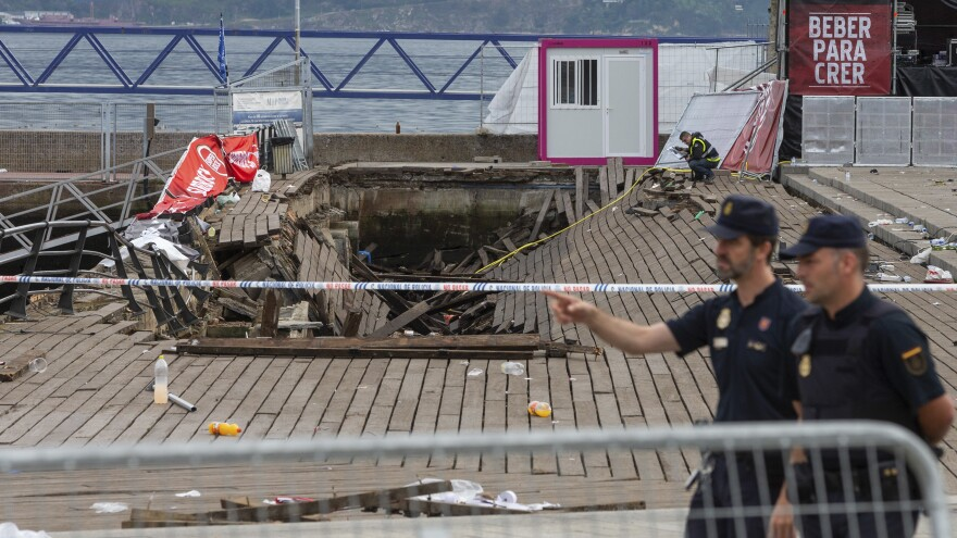 Police officers pass a collapsed oceanside boardwalk in the Spanish port city of Vigo on Monday, hours after the wood planks gave way during a concert.