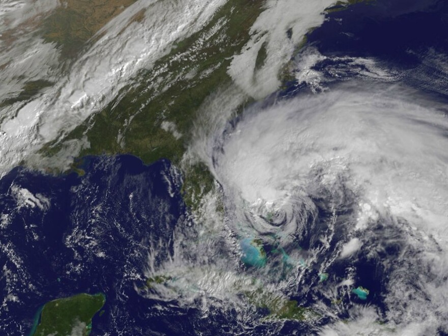 In this satellite image provided Friday by the National Oceanic and Atmospheric Administration, Hurricane Sandy's huge cloud extent of up to 2,000 miles churns over the Bahamas, as a line of clouds associated with a powerful cold front approaches the East Coast of the U.S.