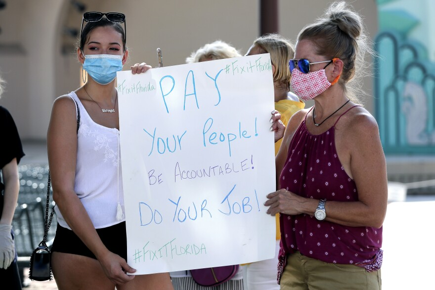 A small group of demonstrators gathers at Lake Eola Park to protest the Florida unemployment benefits system, Wednesday, June 10, 2020, in Orlando, Fla. Many Florida unemployed workers are still trying to apply for and receive unemployment benefits since the start of the coronavirus pandemic.