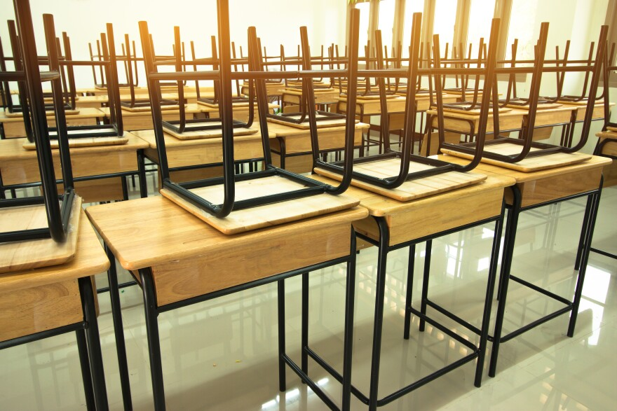 Stock photo of chairs on top of desks in a classroom.