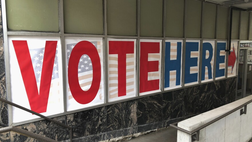 "A ""vote here"" sign marks the entrance to an early voting station in downtown Minneapolis in 2018."
