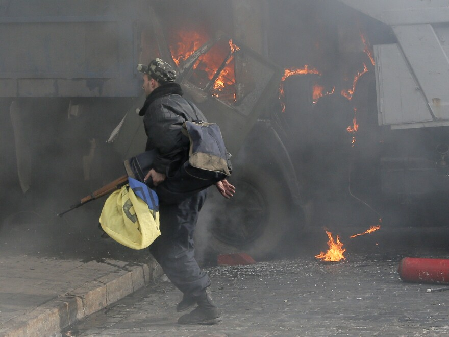 A man with a gun runs along a street during a clash between opposition protesters and riot police at a burning barricades near the Presidential office in Kiev, Ukraine, in February.