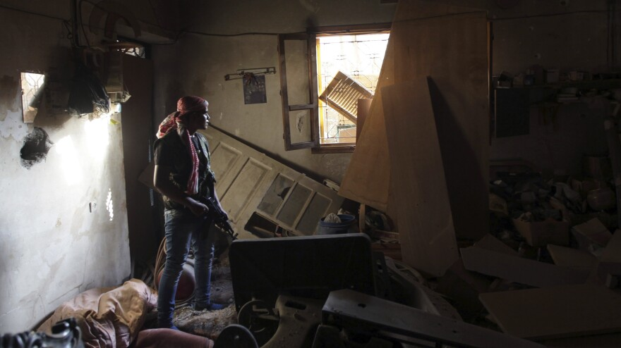 A rebel fighter takes cover inside a damaged building in the eastern Syrian city of Deir al-Zor on Tuesday. The U.S. is training a small number of rebels and has pledged to provide them with arms.