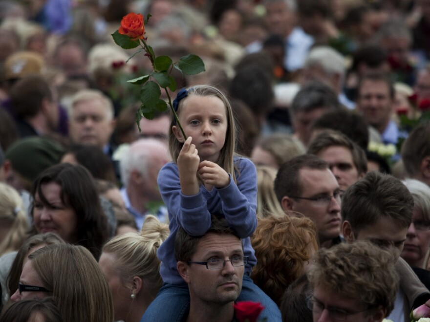 """People gather outside Oslo City Hall to participate in a """"rose march"""" in memory of the victims of Friday's bomb attack and shooting massacre in Norway on Monday, July 25, 2011. Anders Behring Breivik has admitted bombing Norway's capital and opening fire on a political youth group retreat, but he entered a plea of not guilty, saying he wanted to save Europe from Muslim immigration."""