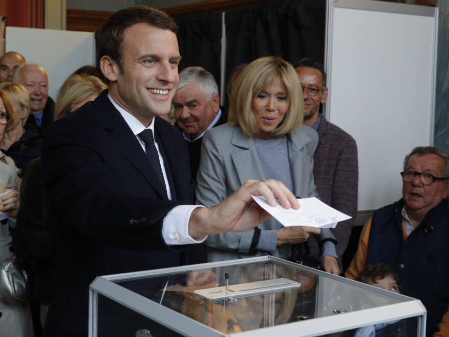 French presidential election candidate for the En Marche ! movement Emmanuel Macron (L) stands next to his wife, Brigitte Trogneux as he casts his ballot at a polling station in Le Touquet, northern France, on April 23, 2017, during the first round of the Presidential election.