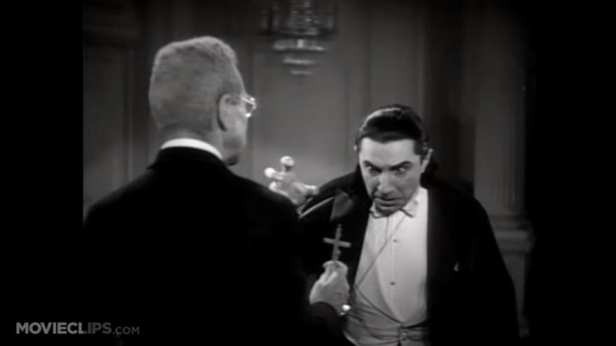 Vampire Count Dracula tries to attack vampire killer Van Helsing before being repulsed by a Christian cross.