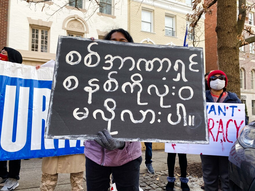 """A demonstrator holds a sign that reads: """"Absolutely against the military/authoritarian state"""" in Burmese during a protest in Washington, D.C., of the recent military coup in Myanmar."""
