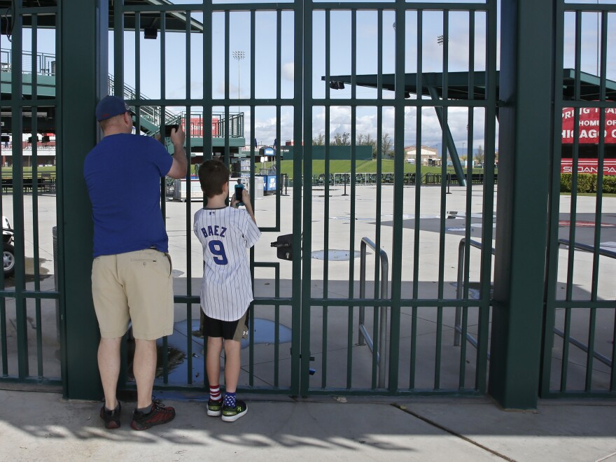Fans take photos through the locked gates at the spring training site of the Chicago Cubs, in Mesa, Ariz., on Friday. Major League Baseball has suspended the rest of its spring training game schedule and delayed opening day by at least two weeks because of the coronavirus outbreak.