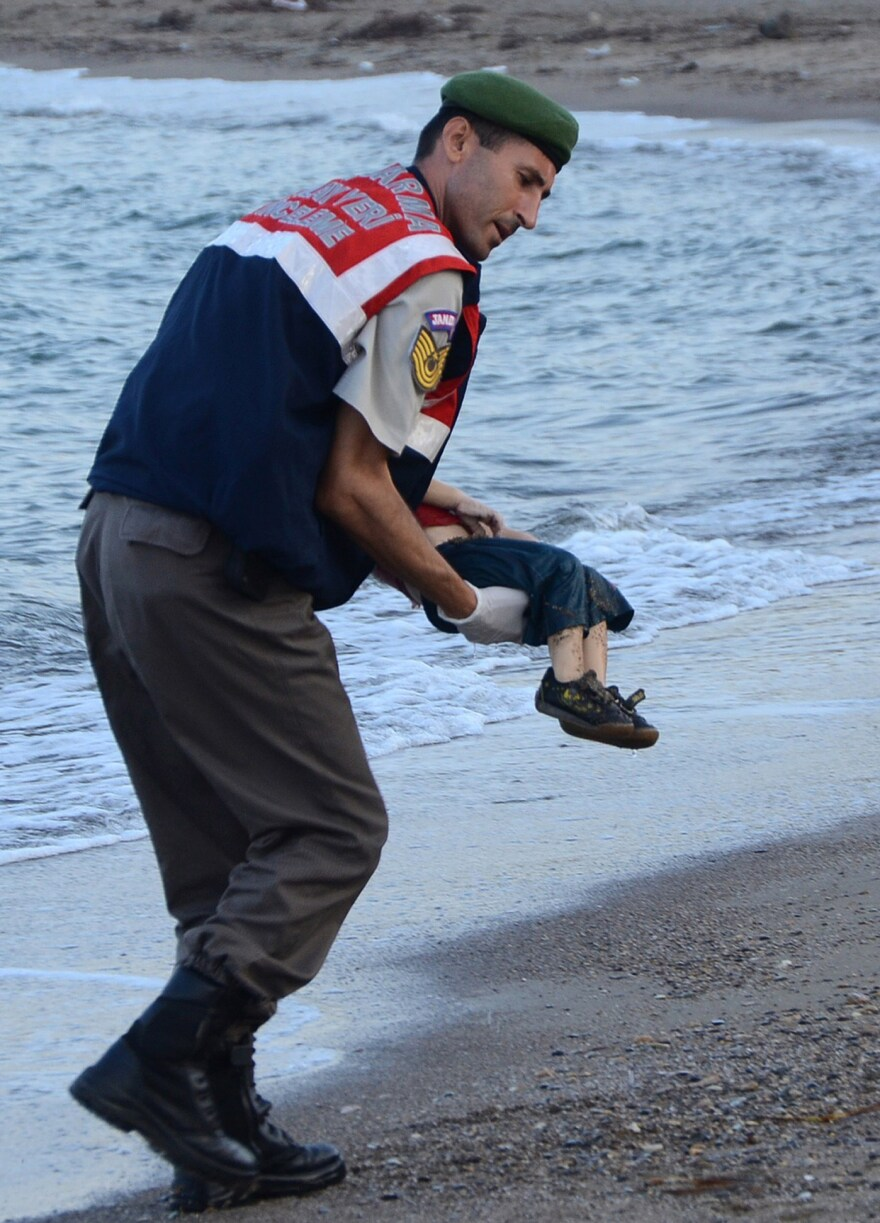 A Turkish police officer carries Aylan Kurdi's dead body off the shores in Bodrum, southern Turkey, on Sept. 2.
