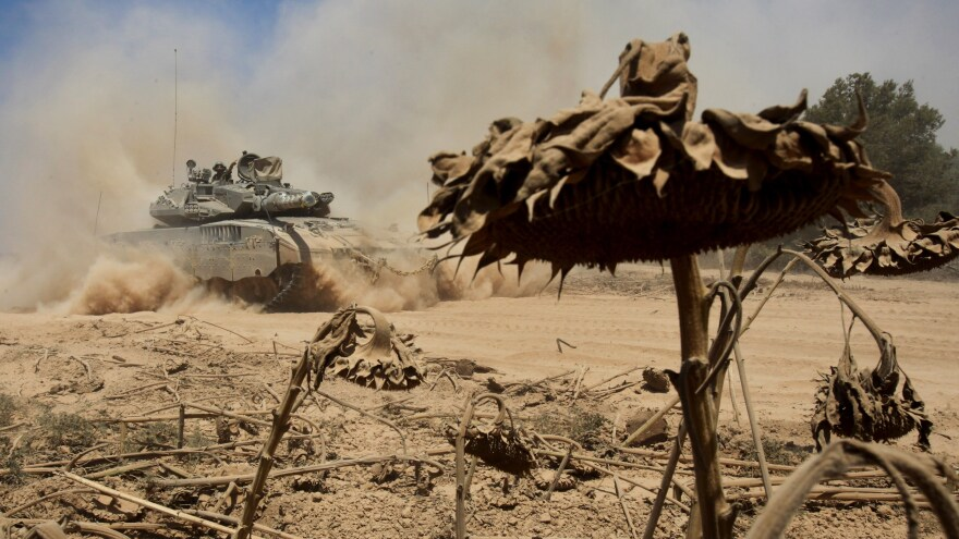 An Israeli tank drives past a field of sunflowers along the border between Israel and the Gaza Strip as they pull out from the Gaza Strip Sunday. At least 10 people died in a strike outside a U.N. school in Gaza shortly after Israel confirmed it was withdrawing some troops from the war-torn area.