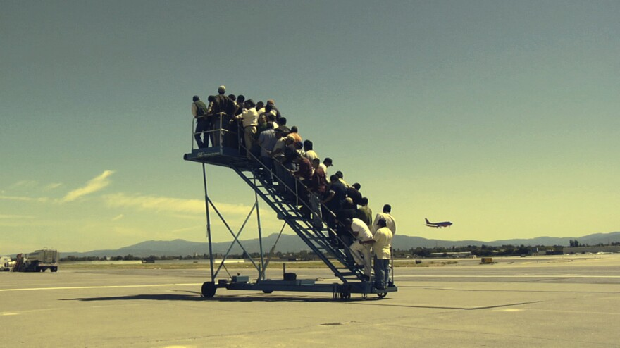 Men wait to board a non-existent plane in Adrian Paci's 2007 video,<em> Centro di permanenza temporanea (Temporary Detention Center).</em>